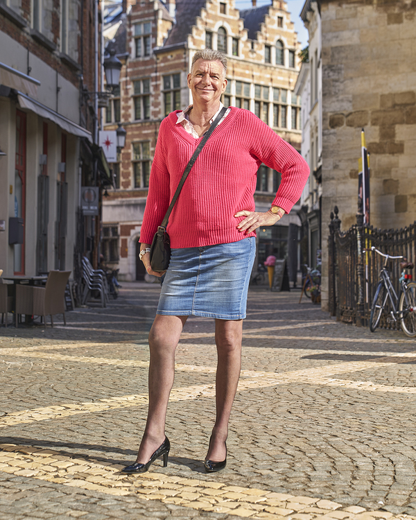 Jack poseert breed lachend in rok en op hoge hakken, te midden van een Antwerps plein