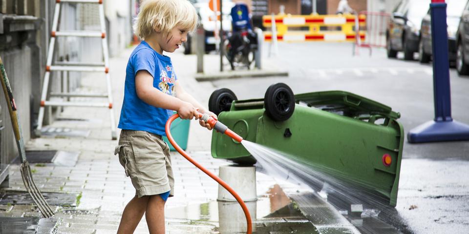 Een jongen poetst de straat tijdens de Lentepoets.