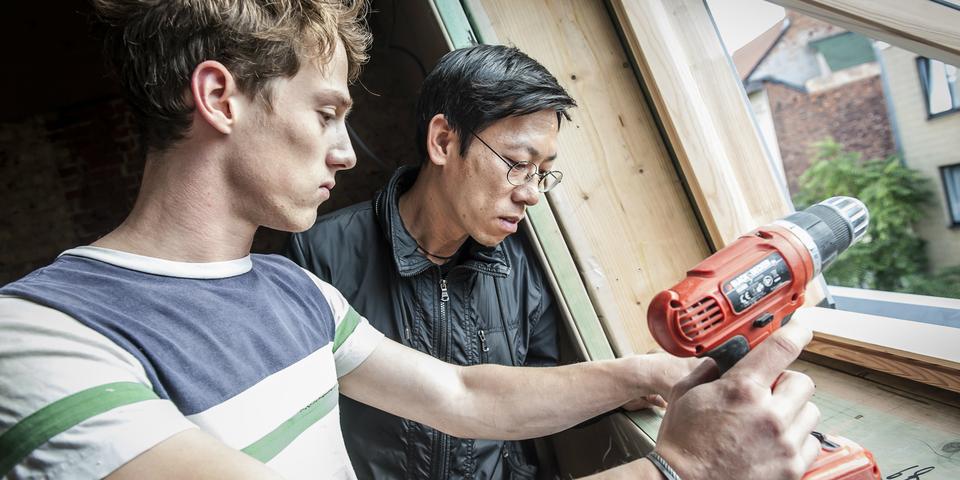 Twee mannen herstellen een raam.