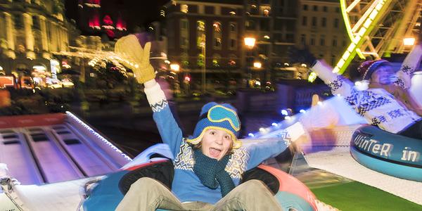 Een kind heeft plezier op de tubing-glijbaan aan het Steenplein tijdens de Winter in An