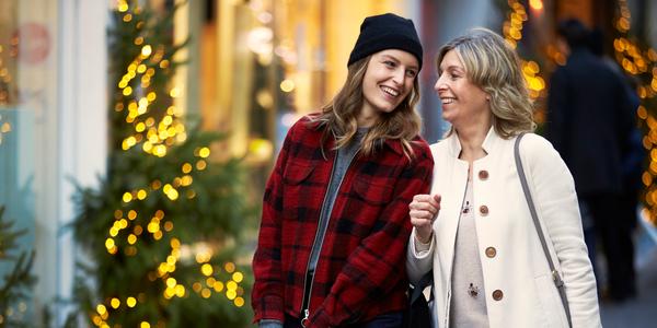 Twee vrouwen lachen naar elkaar op de meir, kerstboom op de achtergrond