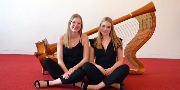 Twee harpistes poseren voor hun instrument