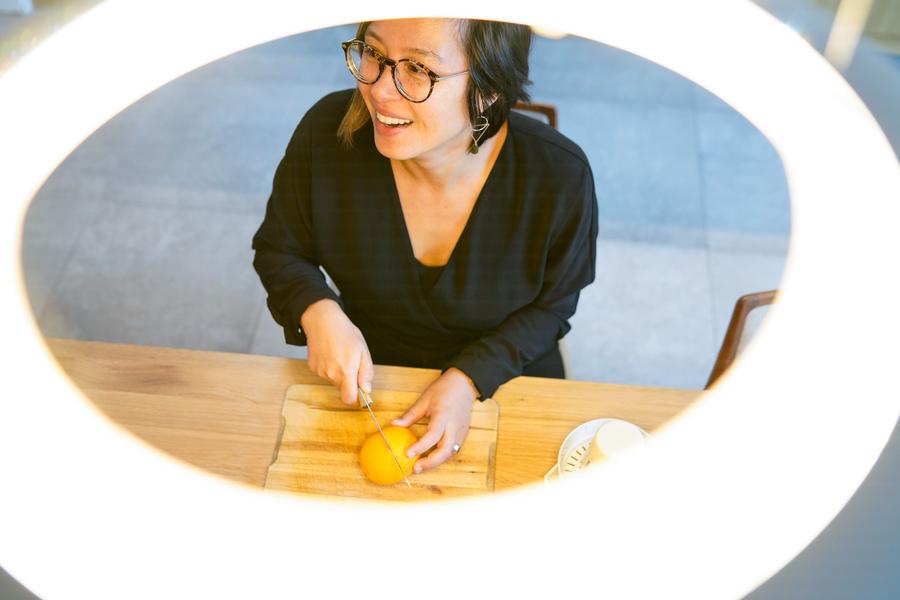 We zien een vrouw aan de keukentafel zitten onder een verlichtingsarmatuur.