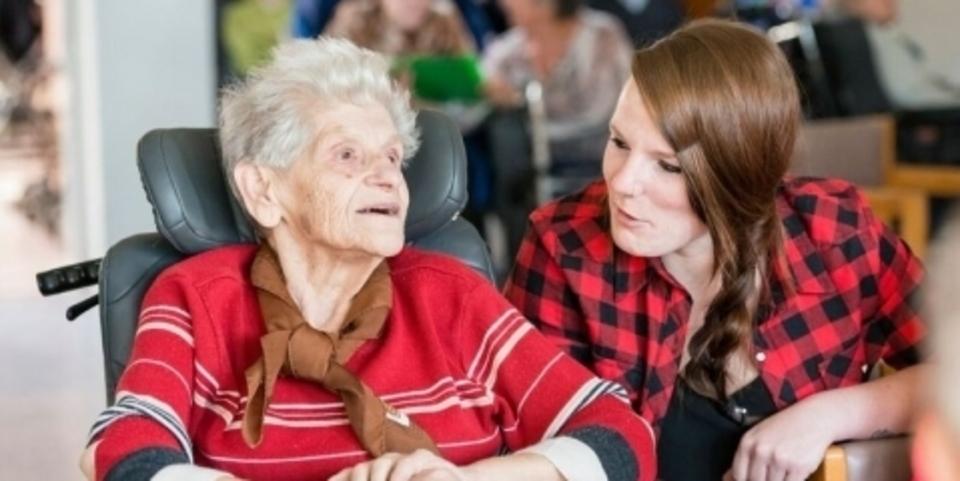 Oude vrouw en jonge mantelzorger