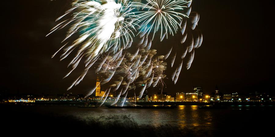 Vuurwerk boven de Schelde en de skyline van Antwerpen.