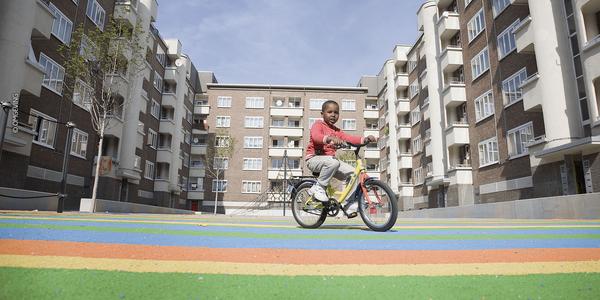 Foto van de Geelhandplaats met gekleurde ondergrond en kind op fiets.