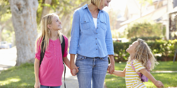 Mama met twee dochters op weg naar school