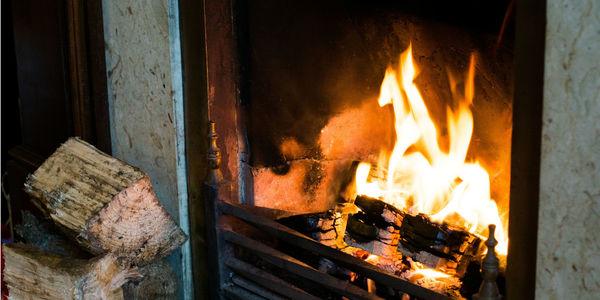 Brandende kachel met houtblokken naast