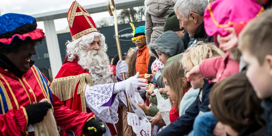 Sinterklaas en een zwarte piet schudden handen met en delen snoep uit aan kinderen.
