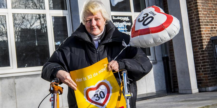 Een dame met rollator poseert met een affiche en ballon waarop 'zone 30' staat.