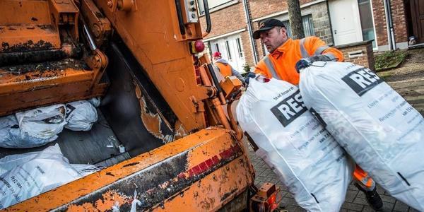 Afvalophaler met 2 vuilniszakken bij vuilniswagen