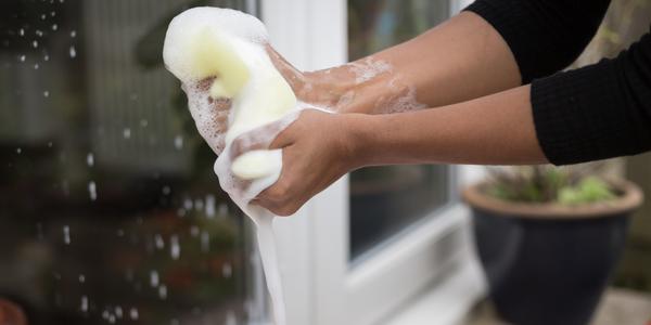Dame wringt een spons uit in het zeepsop.