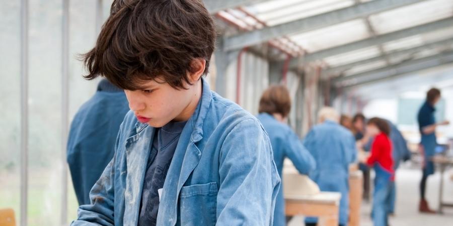 Een jongen is druk in de weer met klei.
