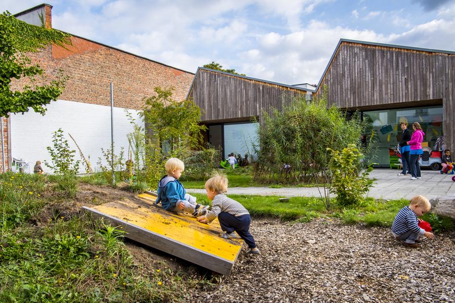 Een deel van de speelzone, met speelheuvel en glijplaat en boomstammen om over te klimmen. Twee kinderen spelen op de glijplaat, een ander kind speelt met de houtsnippers.