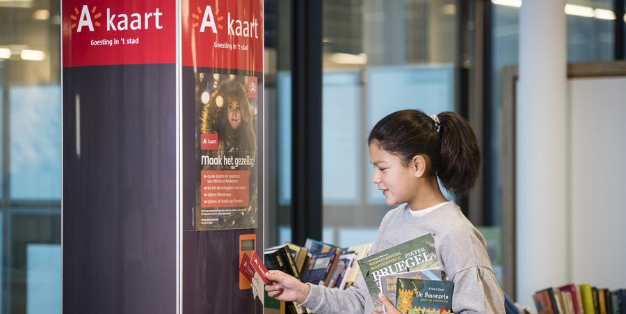 meisje spaart A-kaartpunt aan zuil in bibliotheek