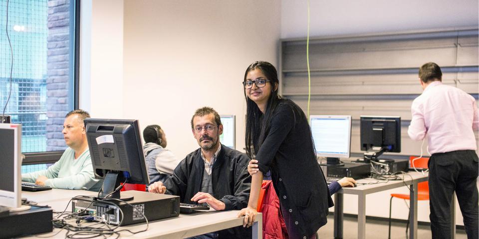 Een burger volgt een computerles in een webpunt met begeleiding.