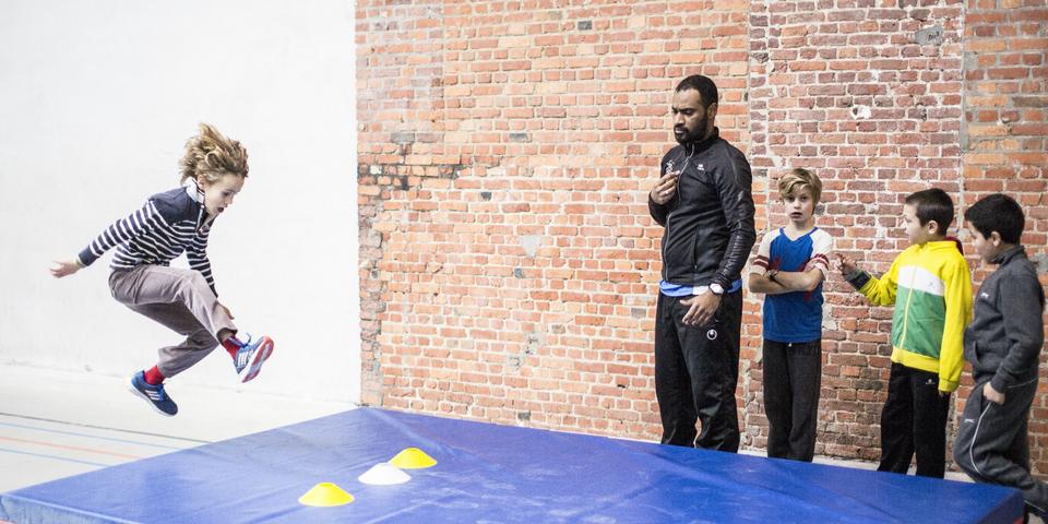 Een vrijwilliger geeft sportles aan kinderen uit de buurt.