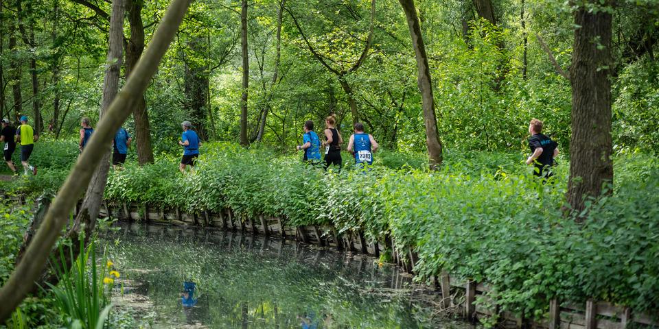 Lopende mensen langs waterloop in park