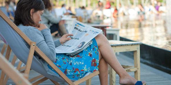 Vrouw leest krant in Park Spoor Noord