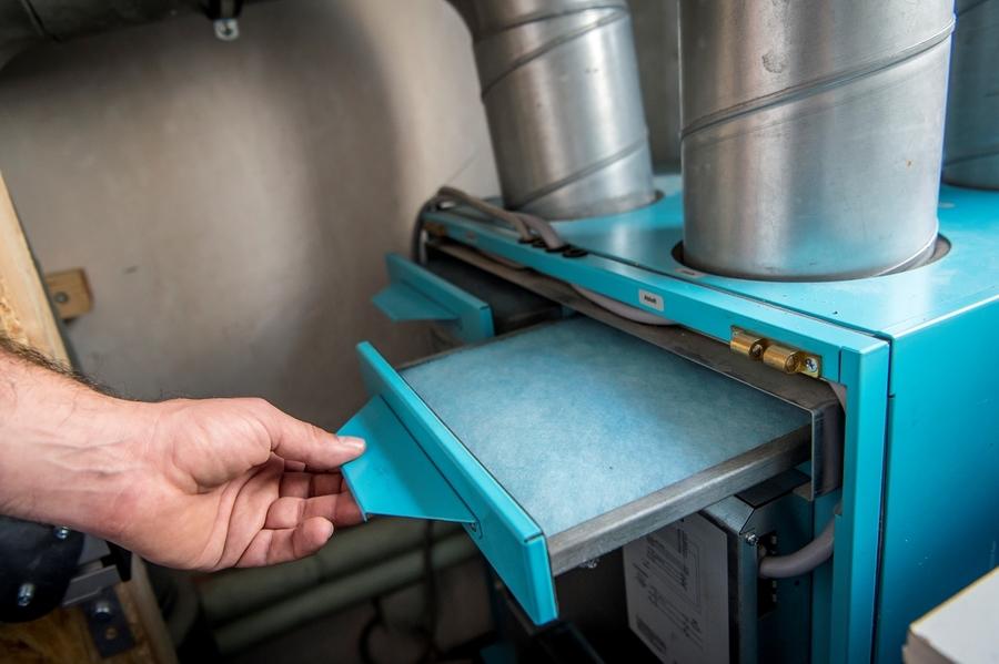 Een filter wordt uit een ventilatie toestel gehaald.