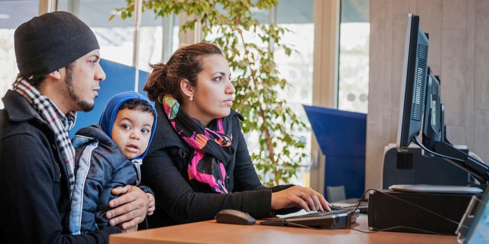 Twee jonge ouders en hun zoontje gebruiken een computer in een Webpunt.