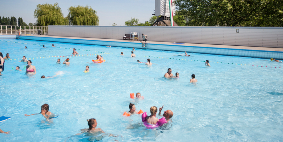 Verschillende mensen zwemmen en maken plezier in openluchtzwembad De Molen.