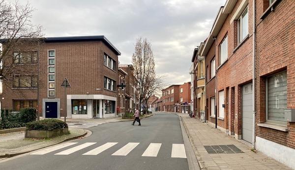 Zicht op het kruispunt van de Lageweg en de Portugesestraat, een vrouw steekt over in de richting van de apotheek op de hoek