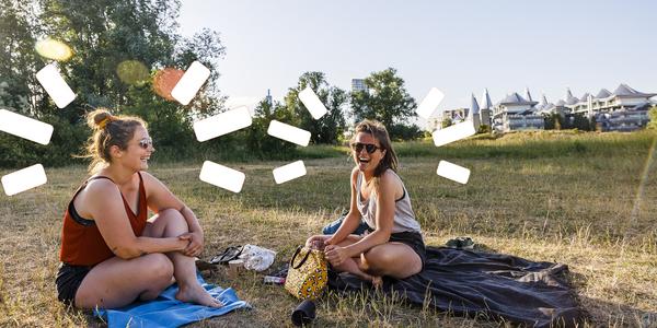 Twee meisjes zitten in het gras en lachen. De zomerzon schijnt.