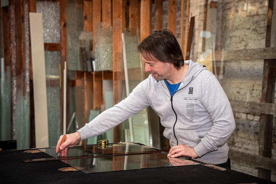 Een man snijdt door glas op een werkblad