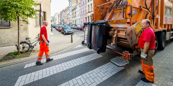 Twee vuilnismannen die afvalcontainers komen ophalen