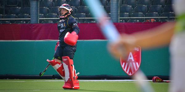 Keeper van de Red Panthers hockeydames staat voor een ledboard met Sporting A label