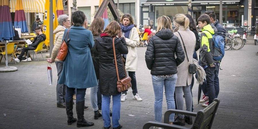 Gids Katrien van Geystelen met een groep luisteraars rond haar