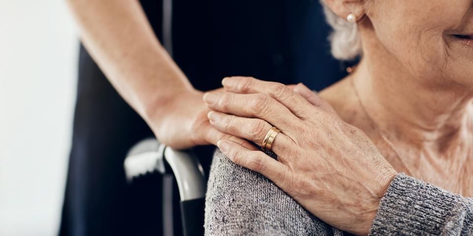 Foto van oudere vrouw in rolstoel die haar hand legt op het hand van een jongere vrouw