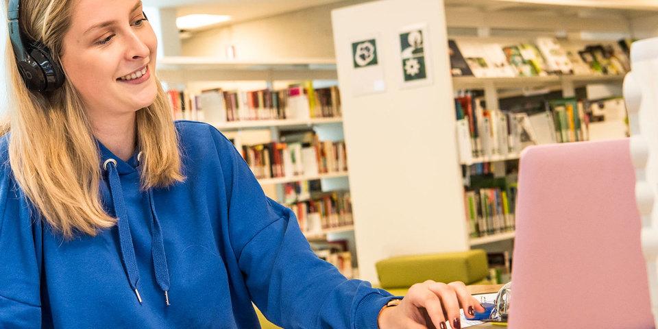 Vrouw volgt online cursus op haar laptop in bib Bist