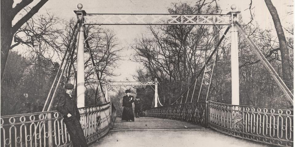 Wandelaars op de hangbrug in het stadspark in 1906.