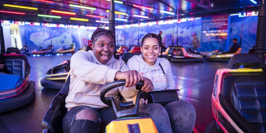 Twee meisjes amuseren zich op de botsauto's