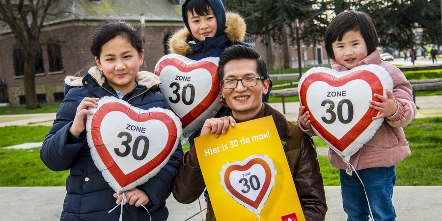 Een papa en zijn drie kinderen poseren met affiches en ballonnen waarop 'zone 30' staat.