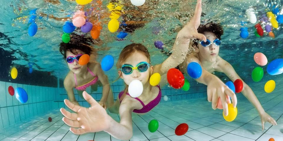 Drie kinderen rapen onder water paaseitjes in het zwembad