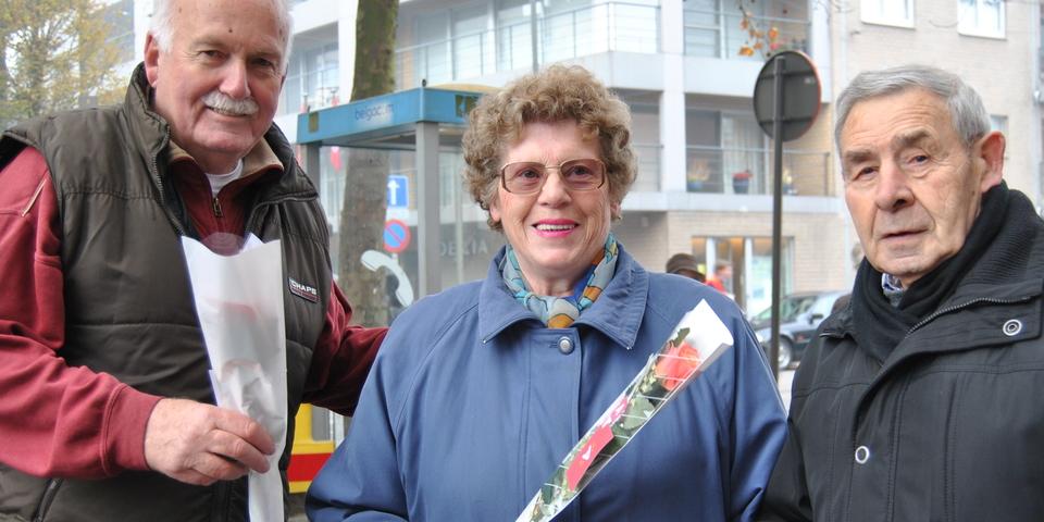 Enkele leden van de Hobokense seniorenraad poseren met een roos