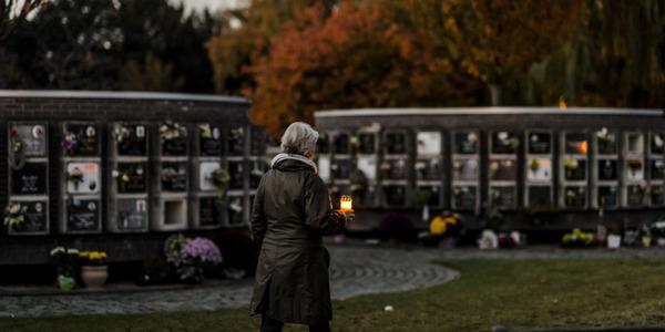 vrouw met kaarsje op begraafplaats