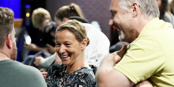 Deelnemers praten met elkaar tijdens een infosessie.