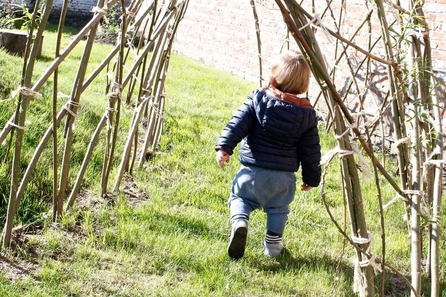 Kind loopt door wilgentunnel