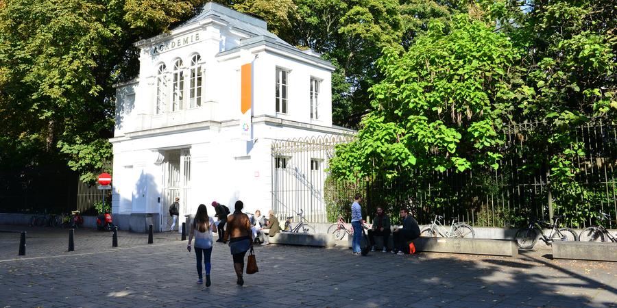 Verschillende studenten wandelen naar of staan voor de Koninklijke Academie voor Schone Kunsten Antwerpen.