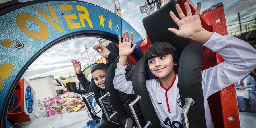 Twee jongetjes met de armen in de lucht op een attractie