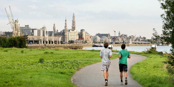 2 lopers joggen met zicht op skyline district Antwerpen