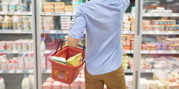 Man met winkelmandje in de supermarkt