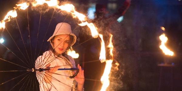 Een artieste toont een vuuract met een vlammende paraplu tijdens het Wintervonk-evenement in Wilrijk.