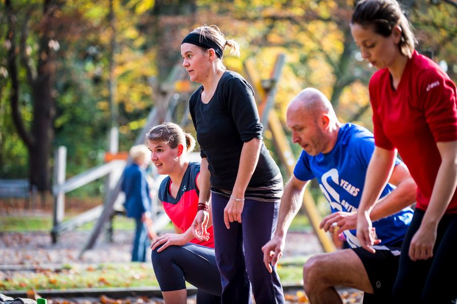 Mannen en vrouwen doen oefeningen in het park