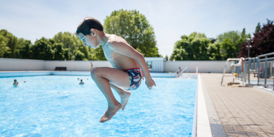 Een jongetje springt in het groot bad van zwembad De Molen op Linkeroever