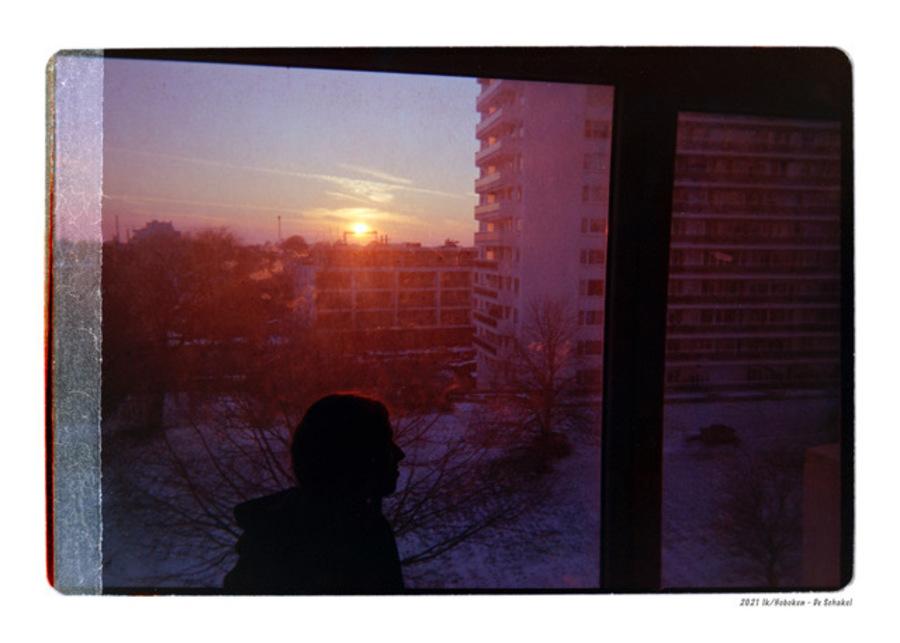 Een meisje achter een raam en de ondergaande zon